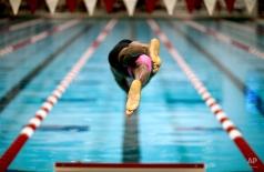 Cullen Jones dives off a starting block in the final heat of the men's 50-meter freestyle at the Bulldog Grand Slam swim meet at the University of Georgia, Saturday, July 12, 2014, in Athens, Ga. (AP Photo/David Goldman)