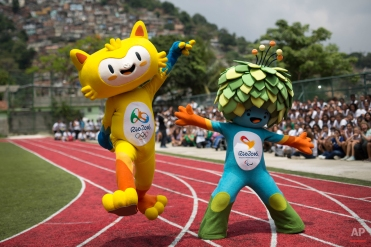 The mascots of the Rio 2016 Olympics, left, and Paralympic Games make their first official appearance at a public school in the Santa Teresa neighborhood of Rio de Janeiro, Brazil, Monday, Nov. 24, 2014. The smiley-faced mascot represents the animal life of Brazil while the mascot for the Paralympics is a mopped-headed doll with leafy hair, meant to represent the vast diversity of the flora in Brazil. (AP Photo/Felipe Dana)