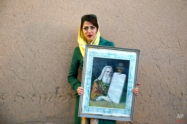 """In this Thursday, Nov. 20, 2014 photo, Iranian Jewish woman Edna Rahmani, 22, holds a painting of Moses with """"The Ten Commandments,"""" after prayers at the Molla Agha Baba Synagogue, in the city of Yazd 420 miles (676 kilometers) south of capital Tehran. (AP Photo/Ebrahim Noroozi)"""