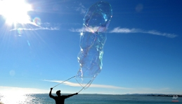 A man makes giant soap bubbles on the Promenade des Anglais in Nice, southeastern France, Sunday, Nov. 16, 2014. Temperatures in the area rose to 19 degrees Celsius (66 Fahrenheit). (AP Photo/Lionel Cironneau)