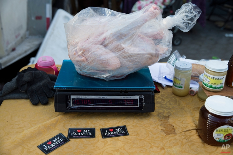 In this Saturday, Nov. 22, 2014, photo, a fresh Thanksgiving turkey is weighed at the Violet Hill Farm market stall at Union Square, in New York. (AP Photo/John Minchillo)