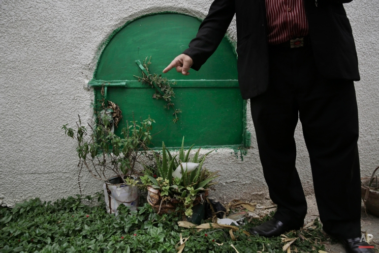 In this Wednesday, Nov. 5, 2014 photo, a man stands in front of the grave of 13-year-old Sohair el-Batea who died undergoing the procedure of female genital mutilation performed by Dr. Raslan Fadl, in Dierb Biqtaris village, on the outskirts of the town of Aga in Dakahliya,120 kilometers (75 miles) northeast of Cairo, Egypt. A verdict is expected Thursday, Nov. 20 in Fadl's trial. Rights advocates say the outcome of this case could set a key precedent for deterring doctors and families in the future. (AP Photo/Nariman El-Mofty)