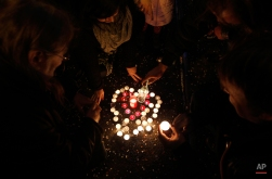 People light and place candles in a shape of heart to commemorate the 25th anniversary of the Velvet Revolution in Prague, Czech Republic, Monday, Nov. 17, 2014. (AP Photo/Petr David Josek)