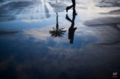 A fan is reflected in a rain puddle as they arrive for the Breeders' Cup horse race at Santa Anita Park Saturday, Nov. 1, 2014, in Arcadia, Calif. (AP Photo/Jae C. Hong)
