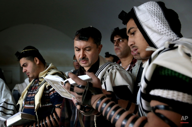 In this Thursday, Nov. 20, 2014 photo, Iranian Jewish men pray at the Molla Agha Baba Synagogue, in the city of Yazd 420 miles (676 kilometers) south of capital Tehran, Iran. More than a thousand people trekked across Iran this past week to visit a shrine in this ancient Persian city, a pilgrimages like many others in the Islamic Republic until you notice men there wearing yarmulkes. (AP Photo/Ebrahim Noroozi)