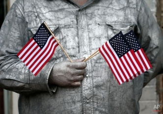 """Street performer John Casey, wearing silver paint as part of his act as """"The Silver Cowboy of Nashville,"""" watches the Veterans Day parade pass by Tuesday, Nov. 11, 2014, in Nashville, Tenn. (AP Photo/Mark Humphrey)"""