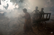 An Indian woman pushes a cart carrying children as they are engulfed in smoke rising from burning garbage on the outskirts of Gauhati, India, Friday, Nov. 14 2014. This week's China-U.S. climate agreement between the world's top two polluters puts pressure on India, No. 3 on the list, to become more energy efficient and should encourage investment in renewable energy. China emits a quarter of the world's greenhouse gases, the United States 15 percent and India about 6 percent. (AP Photo/Anupam Nath)
