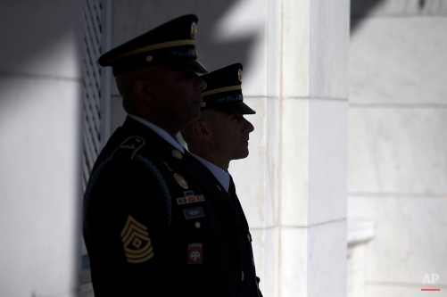 Active duty military service members look on during the annual Veterans Day Observance Ceremony at Arlington National Cemetery in Arlington, Va., Tuesday, Nov. 11, 2014. Americans marked Veterans Day on Tuesday with parades, speeches and military discounts, while in Europe the holiday known as Armistice Day held special meaning in the centennial year of the start of World War I. (AP Photo/Evan Vucci)