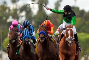 Jockey Florent Geroux, right, celebrates after riding Work All Week to victory in the Breeders' Cup Sprint horse race at Santa Anita Park, Saturday, Nov. 1, 2014, in Arcadia, Calif. (AP Photo/Mark J. Terrill)