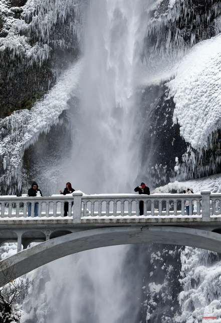 Visitors play with snow and take photos against the backdrop of ice and snow covered walls at Multnomah Falls in the Columbia River Gorge near Bridal Veil, Ore., Friday, Nov. 14, 2014. A Thursday winter storm socked in much of Central and Eastern Oregon, with snow and ice, making travel difficult. (AP Photo/Don Ryan)