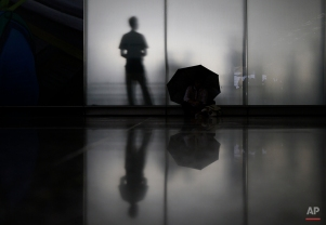 A pro-democracy protester holds an umbrella sitting in front of a glass panel with an airport staff member inside Hong Kong International Airport, Saturday, Nov. 15, 2014. Three students who have led protests for greater democracy in Hong Kong were denied permission to travel to Beijing to meet with China's top officials. (AP Photo/Vincent Yu)