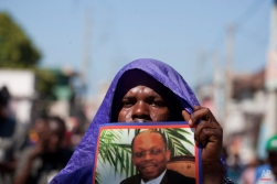 A protester holds up a picture of Haiti's former President Jean Bertrand Aristide during an anti-government protest in Port-au-Prince, Haiti, Tuesday, Nov. 18, 2014. Protesters are demanding the resignation of Michel Martelly. (AP Photo/Dieu Nalio Chery)