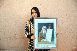 """In this Thursday, Nov. 20, 2014 photo, Iranian Jew Saba Brokhimnejad, 23, holds a painting of Moses with """"The Ten Commandments,"""" after prayers at the Molla Agha Baba Synagogue, in the city of Yazd 420 miles (676 kilometers) south of capital Tehran. (AP Photo/Ebrahim Noroozi)"""