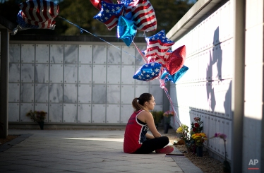 Aimee Tarte visits her father's grave on Veterans Day at the South Florida National Cemetery in Lake Worth, Fla., Tuesday, Nov. 11, 2014. He was a Vietnam veteran, who died in January. (AP Photo/J Pat Carter)