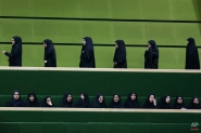 A group of female spectators leave as another group follows a debate of the Iranian parliament on a vote of confidence for nominee for the post of science minister Fakhroddin Ahamadi Danesh Ashtiani proposed by the President Hassan Rouhani, in Tehran, Iran, Tuesday, Nov. 18, 2014. Iran's parliament rejected Rouhani's nominee for the post of science minister over his pro-reform tendencies. In October the parliament rejected Mahmoud Nili Ahmadabadi, another nominee for the same post; the same body dismissed former-Science Minister Reza Faraji Dana in August over similar allegations. (AP Photo/Vahid Salemi)