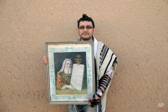 """In this Friday, Nov. 21, 2014 photo, Iranian Jew Mehrdad Sasanifar, 35, holds a painting of Moses with """"The Ten Commandments,"""" after prayers at the Molla Agha Baba Synagogue, in the city of Yazd 420 miles (676 kilometers) south of capital Tehran. (AP Photo/Ebrahim Noroozi)"""