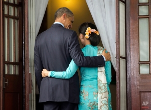 U.S. President Barack Obama, left, and Myanmar's opposition leader Aung San Suu Kyi, right, walk back to her home following the conclusion of their joint news conference in Yangon, Myanmar, Friday, Nov. 14, 2014. (AP Photo/Pablo Martinez Monsivais)