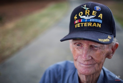 A retired Korean War Veteran, Wheeler Forshee, sits and watches the Veterans Day parade Tuesday, Nov. 11, 2014, in Montgomery, Ala. (AP Photo/Brynn Anderson)