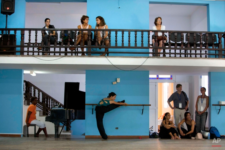 In this Oct. 30, 2014 photo, people watch dancers practice at the National Cuban Ballet dance house in Havana, Cuba. Dozens of Cuban dancers returned to the island to be part of the 24th International Ballet Festival of Havana, where several workshops were dedicated to Fernando Alonso, one of the founders of the National Ballet of Cuba who died last year. (AP Photo/Franklin Reyes)