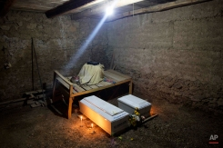 In this Oct. 29, 2014 photo, a lamp shines inside the dirt floor home of the Huaman family where the coffins of Felix Huaman and his brother-in-law Narcizo Cusiche are placed for a one day wake, as is custom in Huallhua, Peru. Huaman and Cusiche were killed on June 14, 1990 defending the town as members of the citizen self-defense force so villagers could escape from Shining Path militants, but their remains were only recently exhumed. Hundreds of such cases, most until now barely registered, are coming to light as forensic anthropologists methodically unearth victims of Peru's 1980-2000 dirty war absent government fanfare. (AP Photo/Rodrigo Abd)