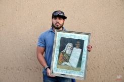 """In this Thursday, Nov. 20, 2014 photo, Iranian Jew Saman Davoudi, 24, holds a painting of Moses with """"The Ten Commandments,"""" after prayers at the Molla Agha Baba Synagogue, in the city of Yazd 420 miles (676 kilometers) south of capital Tehran. (AP Photo/Ebrahim Noroozi)"""