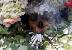 """A human skull or """"natita"""" is crowned with flowers and surrounded by offerings of coca leaves, flower petals and cigarettes, during the Natitas Festival, outside the Cementerio General chapel , in La Paz, Bolivia, Saturday, Nov. 8, 2014. Followers believe the skulls or natitas have miraculous powers, providing protection and granting favors that range from finding a job to helping their favorite soccer team win. (AP Photo/Juan Karita)"""