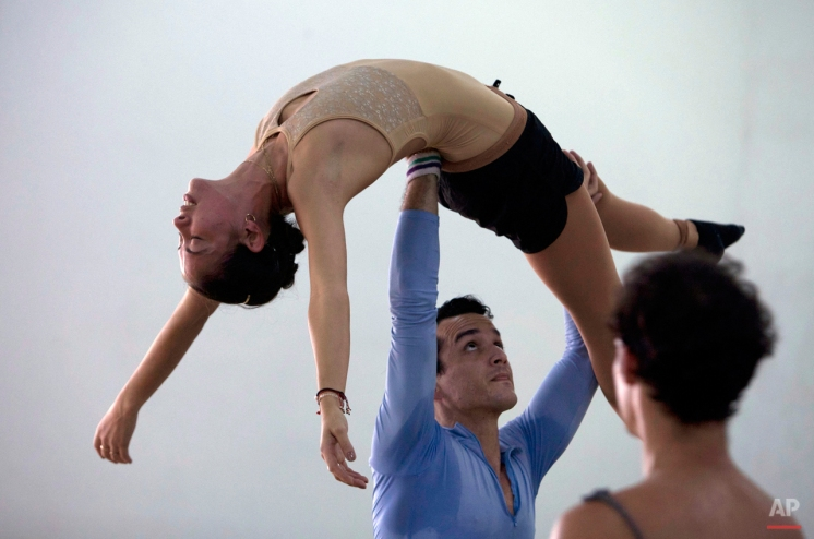 In this Oct. 29, 2014 photo, Cuban dancer Javier Torres, who is a member of the Northern Ballet of Great Britain, lifts up Cuban premier ballerina Anette Delgado during training at the 24th international Ballet festival in Havana, Cuba. Festival goers were treated to new works by Torres, choreographer Luis Serrano, and American Ballet Theatre star Xiomara Reyes. (AP Photo/Franklin Reyes)