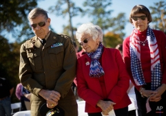 Carol Rump, center, looks over at her husband, U.S. Army Korean War veteran Urban Rump, 83, left, as he wears his old uniform while joined by Dolores Moore, right, during a moment of silence at a Veterans Day ceremony at the Atlanta History Center, Tuesday, Nov. 11, 2014, in Atlanta. (AP Photo/David Goldman)