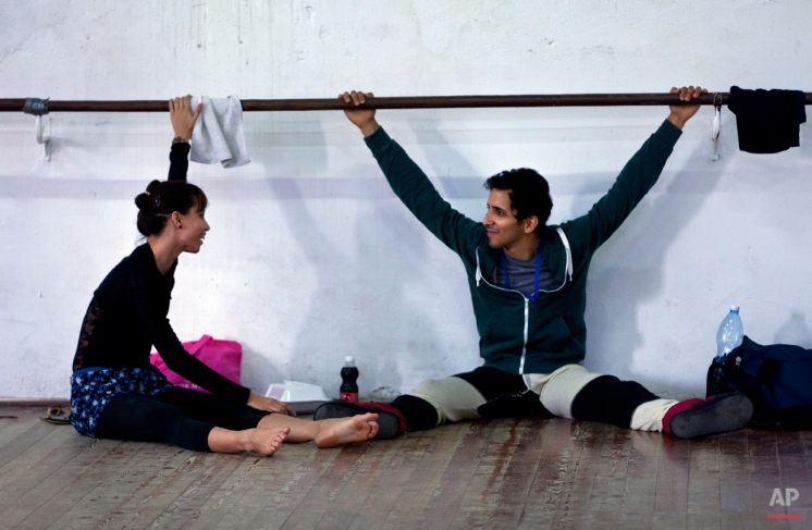 In this Oct. 29, 2014 photo, Cuban dancer Rodrigo Almarales talks with a ballerina as they take a break at the National Cuban Ballet dance house during the 24th International Ballet Festival in Havana, Cuba. Almarales is a member of the Cincinnati Ballet whose dancer parents left the island decades ago. With Cuba relaxing its attitude toward those living abroad, the National Ballet welcomed their prodigal children with enthusiasm. (AP Photo/Franklin Reyes)