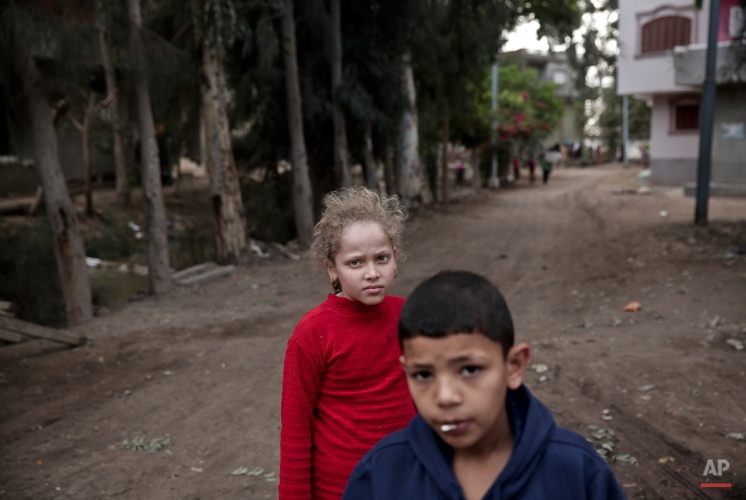 In this Wednesday, Nov. 5, 2014 photo, Egyptian school children walk on a street, near the home of 13-year-old Sohair el-Batea who died undergoing the procedure of female genital mutilation performed by Dr. Raslan Fadl, in Dierb Biqtaris village, on the outskirts of the town of Aga in Dakahliya,120 kilometers (75 miles) northeast of Cairo, Egypt. (AP Photo/Nariman El-Mofty)