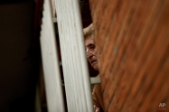 A neighbor watches from her window while Laura De La Rosa Munoz, 30, center, and her family are evicted from the apartment they were occupying in Madrid, Spain, Friday, Nov. 14, 2014. The apartment is property of Bankia bank and Laura unemployed, and caring of her daughter Alba 13, and her sons Angel 11 Moises 9, and Ezequiel 6, occupied it one year ago. The family have tried to negotiate to pay a low rent but the Bankia bank demanded their eviction. Victims' Mortgage Platform (PAH) tried to stop the process but the police evicted the family. (AP Photo/Daniel Ochoa de Olza)