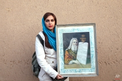 """In this Thursday, Nov. 20, 2014 photo, Iranian Jew Ghazal Noghrehian, 27, holds a painting of Moses with """"The Ten Commandments,"""" after prayers at the Molla Agha Baba Synagogue, in the city of Yazd 420 miles (676 kilometers) south of capital Tehran. (AP Photo/Ebrahim Noroozi)"""