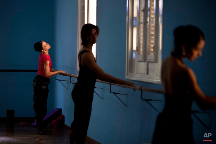 In this Oct. 30, 2014 photo, premier ballerina Viengsay Valdes, left, warms up at the National Cuban Ballet dance house in Havana, Cuba. The National Ballet of Cuba was founded in 1948 by Fernando Alonso and his wife, premier ballerina Alicia Alonso, who both rose to fame in the late 1940s in New York. It is considered one of the crown jewels of Cuban culture, prestige. (AP Photo/Franklin Reyes)