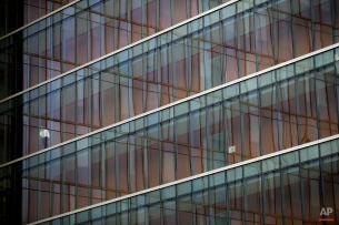 A man leans on a glass wall of the LAPD headquarters building as he talks on the phone in Los Angeles on Thursday, Nov. 13, 2014. (AP Photo/Jae C. Hong)