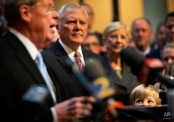"""William Isakson, 6, right, looks up toward his grandfather, Sen. Johnny Isakson, R-Ga., far left, as he speaks during a news conference to announce his re-election bid for the 2016 campaign at the state Capitol, Monday, Nov. 17, 2014, in Atlanta. The Republican, who'll be seeking his third term, told about 200 supporters Monday that he wants to keep fighting to build up Georgia's infrastructure, pass a balanced budget amendment and reduce federal spending. Gov. Nathan Deal praised Isakson as a """"stable conservative leader."""" (AP Photo/David Goldman)"""