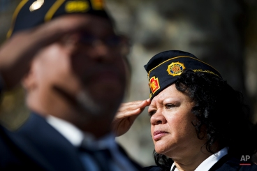 Army veteran Renee Anderson salutes during a ceremony on Veterans Day, Tuesday, Nov. 11, 2014, at the The All Wars Memorial to Colored Soldiers and Sailors in Philadelphia. Americans marked Veterans Day on Tuesday with parades, speeches and military discounts, while in Europe the holiday known as Armistice Day held special meaning in the centennial year of the start of World War I. (AP Photo/Matt Rourke)
