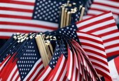 A member of the Daughters of the American Revolution holds a bundle of American flags to be passed out before a Veterans Day parade in Indianapolis, Tuesday, Nov. 11, 2014. (AP Photo/Michael Conroy)