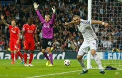 Real Madrid's Karim Benzema, right, celebrates after scoring the opening goal during a Group B Champions League soccer match between Real Madrid and Liverpool at the Santiago Bernabeu stadium in Madrid, Spain, Tuesday Nov. 4, 2014. (AP Photo/Andres Kudacki)