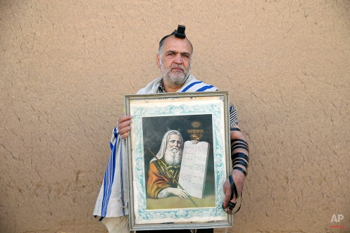 """In this Friday, Nov. 21, 2014 photo, Iranian Jew Mashaallah Pesar Kohan, 54, holds a painting of Moses with """"The Ten Commandments,"""" after prayers at the Molla Agha Baba Synagogue, in the city of Yazd 420 miles (676 kilometers) south of capital Tehran. (AP Photo/Ebrahim Noroozi)"""