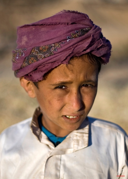 A Yemeni boy poses for a picture while his father threshes grain from chaff during the harvest season on the outskirts of Sanaa, Yemen, Saturday, Nov. 15, 2014. (AP Photo/Hani Mohammed)