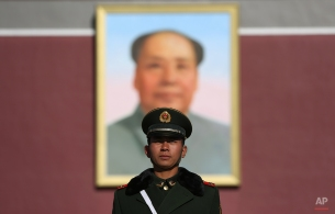 A Chinese paramilitary police stands in front a portrait of late Chinese leader Mao Zedong outside the Forbidden city, Beijing, China on Wednesday, Nov. 12, 2014. (AP Photo/Aaron Favila)