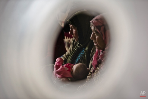Seen through an air vent of a tent a Syrian Kurdish refugee woman from the Kobani area holds a child on a cold morning at a camp in Suruc, on the Turkey-Syria border Monday, Nov. 17, 2014. Kobani, also known as Ayn Arab, and its surrounding areas, has been under assault by extremists of the Islamic State group since mid-September and is being defended by Kurdish fighters. (AP Photo/Vadim Ghirda)