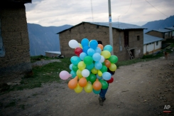 In this Oct. 28, 2014 photo, a government social worker carries balloons after a training course for young leaders in Ayahuanco, Peru. Though the Shining Path was defeated two decades ago, cocaine-funded rebel remnants continue to hound Peru's security forces in the remote region. (AP Photo/Rodrigo Abd)