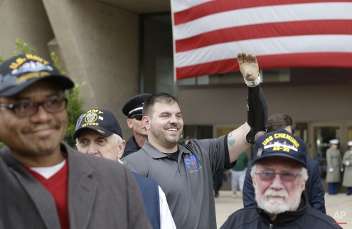 Retired US Army Staff Sergeant Travis Mills of the 82nd Airborne waves to a fellow veteran as he watches a Veterans Day parade in downtown Dallas, Tuesday, Nov. 11, 2014. Mills was wounded in action by an IED in Afghanistan becoming the 4th of 5 quadruple U.S. service amputees in the war in Afghanistan. (AP Photo/LM Otero)