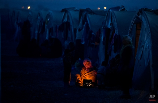 An elderly Syrian Kurdish refugee woman from the Kobani area, warms up by a fire at a camp in Suruc, on the Turkey-Syria border Monday, Nov. 10, 2014. Kobani, also known as Ayn Arab, and its surrounding areas, has been under assault by extremists of the Islamic State group since mid-September and is being defended by Kurdish fighters. (AP Photo/Vadim Ghirda)