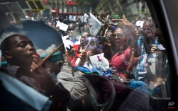 Kenyan women protest for the right to wear whichever clothes they want, accompanied by a male supporter, left, seen reflected and through the windows of a minibus, at a demonstration in downtown Nairobi, Kenya Monday, Nov. 17, 2014. A recent incident in which a mob of men surrounded a woman and tore her clothes off, leaving her naked on the street in front of a bus stop after alleging that she was improperly dressed, is one of several such videos that have surfaced online in recent days leading to a groundswell of anger that on Monday prompted around 1000 demonstrators, including a number of men supporting the women's cause, to march through the capital and protest online using the hashtag #MyDressMyChoice. (AP Photo/Ben Curtis)