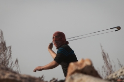 A Palestinian uses a sling shot during clashes with Israeli forces following a protest against Israeli restrictions to Al-Aqsa Mosque in Jerusalem, at the Qalandia checkpoint near the West Bank city of Ramallah, Friday, Nov. 14, 2014. In recent weeks, police had barred Muslim men younger than 35 to try and quell violent protests by Palestinians, who have clashed with police in response to visits to the holy site by Jewish worshippers. (AP Photo/Majdi Mohammed)