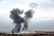Smoke rises from the Syrian city of Kobani, following airstrikes by the US led coalition, seen from a hilltop outside Suruc, on the Turkey-Syria border Monday, Nov. 17, 2014. Kobani, also known as Ayn Arab, and its surrounding areas, has been under assault by extremists of the Islamic State group since mid-September and is being defended by Kurdish fighters. (AP Photo/Vadim Ghirda)