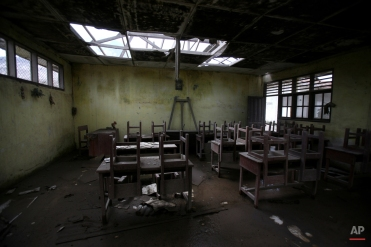 In this Oct 17, 2014, photo, chairs rest on tables in an empty classroom at an elementary school in the abandoned village of Simacem, North Sumatra, Indonesia. The village was abandoned after its people were evacuated following the eruption of Mount Sinabung. (AP Photo/Binsar Bakkara)