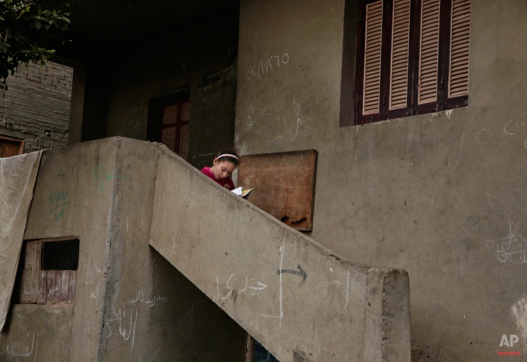 In this Wednesday, Nov. 5, 2014 photo, an Egyptian girl reads a book on a stairway, near the home of 13-year-old Sohair el-Batea who died undergoing the procedure of female genital mutilation performed by Dr. Raslan Fadl, in Dierb Biqtaris village, on the outskirts of Aga town in Dakahliya,120 kilometers (75 miles) northeast of Cairo, Egypt. (AP Photo/Nariman El-Mofty)